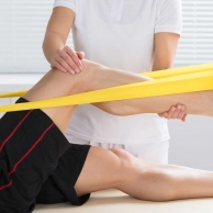 Physiotherapist Giving Treatment With Exercise Band